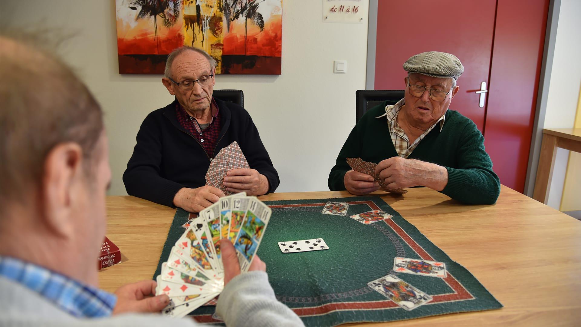 3 résidents de la Résidence des Acacias jouant aux cartes